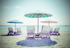 Retro filtered picture of beach chairs and umbrellas. Stock Photo