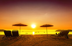 Retro filtered picture of beach chairs and umbrellas on sand. Stock Images