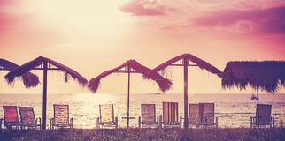 Retro filtered picture of beach chairs and umbrellas at sunset. Stock Photography