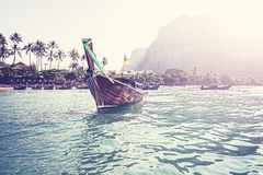Retro filtered picture of boat and tropical island Stock Photography