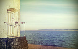 Retro filtered picture of a door to old lighthouse. Royalty Free Stock Images