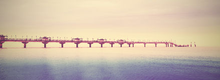 Retro filtered picture of long pier into the sea Stock Images
