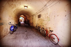 Retro filtered picture of neglected passage with bikes. Royalty Free Stock Image