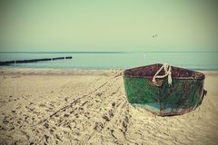Retro filtered picture of an old rusty steel boat on the beach Royalty Free Stock Photos
