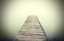 Retro filtered picture of old wooden pier into dense fog Royalty Free Stock Image