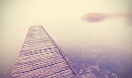Retro filtered picture of old wooden pier into dense fog Royalty Free Stock Photography