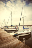 Retro filtered picture of yachts at pier Royalty Free Stock Photo