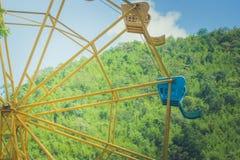 Retro fine d'annata di immagine sulla parte della ruota di ferris variopinta con il fondo verde del cielo blu e dell'albero Fotografia Stock Libera da Diritti