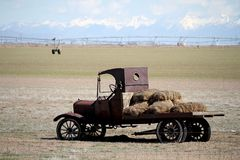Retro flatbed truck with hay bales in a farm field. This is a vintage flatbed truck with hay bales on the back area.  The vehicle is parked in a farm field in stock photo
