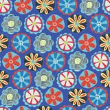 Retro flower seamless vector background. 1960s, 1970s floral design. Red, blue, and yellow doodle flowers on a blue background. Vintage flower pattern for royalty free illustration
