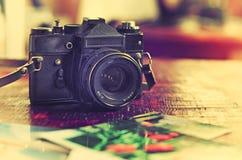 Retro fotokamera, film och gamla foto på tabellen royaltyfria bilder