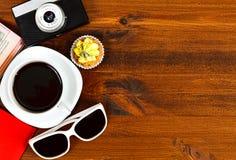 Retro- Fotokamera, Kaffeetasse, Pass, Sonnenbrille und kleiner Kuchen Stockfotos