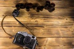 Retro fotokamera med den fotofilmen och linsen på trätabellen Royaltyfria Foton