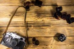 Retro- Fotokamera mit Fotofilm und -linse auf Holztisch Stockfotos