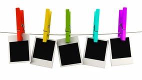 Retro- Fotorahmen, der an einem Seil auf mehrfarbigen Wäscheklammern hängt Stockfotografie