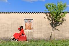 Retro- Frau, die auf einem Koffer sitzt lizenzfreies stockfoto