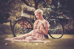 Retro- Frau, die auf einer Wiese sitzt Lizenzfreie Stockfotos