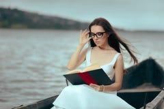 Retro- Frau, die ein Buch in einem Weinlese-Boot liest stockfoto