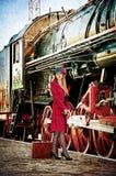 Retro- Frau mit Koffer an der Bahnstation. Stockfoto