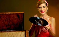 Retro- Frau mit Musikvinylaufzeichnung Mädchenstift-obenart, die rotes Kleid trägt Lizenzfreie Stockfotos