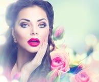 Retro- Frauenporträt in den rosa Rosen Lizenzfreies Stockbild