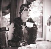 Retro- Frauenzwanziger jahre - dreißiger Jahre, die mit Tasse Tee sitzen Lizenzfreie Stockfotografie