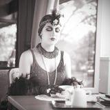Retro- Frauenzwanziger jahre - dreißiger Jahre, die mit Tasse Tee sitzen Lizenzfreies Stockfoto