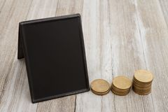 Retro freestanding chalkboard with gold coins on weathered wood stock photography
