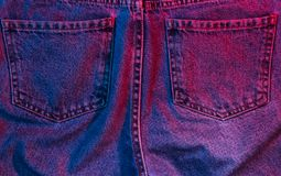 Texture of crumpled pocket jeans. Retro futurism background. Texture of crumpled pocket jeans with red-blue neon light. 80s stock photos