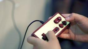Retro gamepad e mani classici del giocatore Giocatore che preme i bottoni e gioco video d archivio
