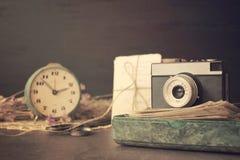 Retro gammal kamera med högen av foto, bokstäver, malakitasken och antikvitetklockor på träbakgrund Minnen nostalgi, arkivfoto