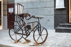 Retro gammal rostig cykel för tappning på den dekorativa gatan Arkivfoton