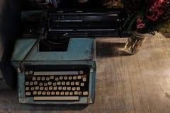Retro gammal tappningskrivmaskin med en vas av blommor Royaltyfri Bild