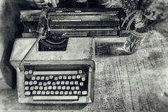 Retro gammal tappningskrivmaskin med en vas av blommor med svart a Arkivbild