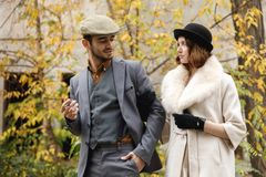 A retro gangster couple are walking around holding hands and looking at each other. The guy is smoking a cigar. Outdoors Royalty Free Stock Image