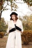 Retro gangsterska dziewczyna w czarnym kapeluszu, futerkowym żakiecie i czarnych rękawiczkach w jesień parku, Zdjęcia Royalty Free