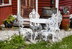 Retro garden furniture. White metallic garden furniture in retro style in a garden of a red wooden house. Flowers and grass around Royalty Free Stock Image