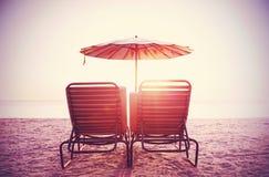Retro gefiltreerd beeld van ligstoelen en paraplu op zand royalty-vrije stock fotografie