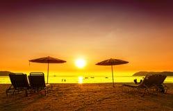 Retro gefiltreerd beeld van ligstoelen en paraplu's op zand Stock Afbeeldingen