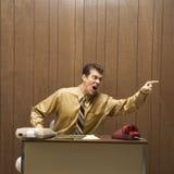 Retro- Geschäftsszene des verärgerten Mannes am Schreibtisch. lizenzfreies stockfoto