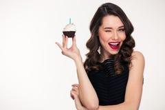 Retro gestileerde verjaardag van de vrouwenholding cupcake met kaars en het knipogen Royalty-vrije Stock Foto's