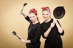 Retro gestileerde vrouwen die pret met keukentoebehoren hebben Royalty-vrije Stock Foto's