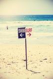 Retro- getontes Schwimmen und Brandung unterzeichnen auf dem Strand Stockfoto