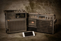 Retro ghetto blaster. The still life retro ghetto blaster and new smartphone on grunge background royalty free stock images