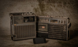 Retro ghetto blaster. The still life retro ghetto blaster and new smartphone on grunge background stock photography