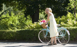 Retro Girl. Pretty young woman standing beside retro bicycle in outdoor setting Stock Photography