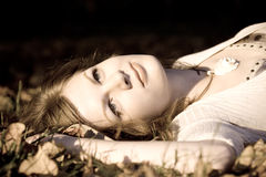 Retro Girl autunm leaves. Portrait of a Beautiful  retro Girl lying in autunm leaves Royalty Free Stock Photo