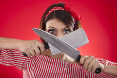 Retro girl looking between two kitchen knives Royalty Free Stock Image