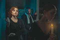 Retro girl and a man looking at her. Retro men and a red haired girl looking reproachfully at the girl with a candle royalty free stock photos