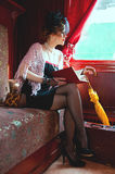 Retro girl reading book in  wagon train. Royalty Free Stock Images